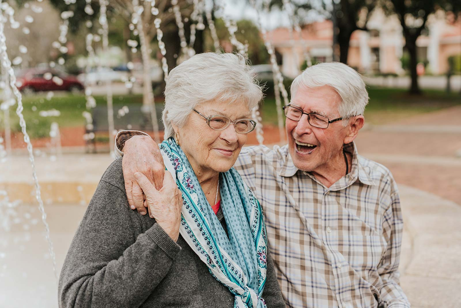 Senior man with arm around senior woman with fountain in background behind them