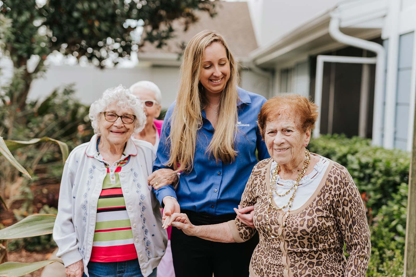 Femal staff member walking with group of senior women holding hands