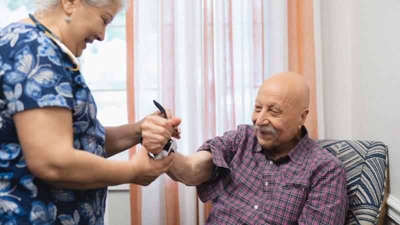Nurse taking blood pressure reading from senior man